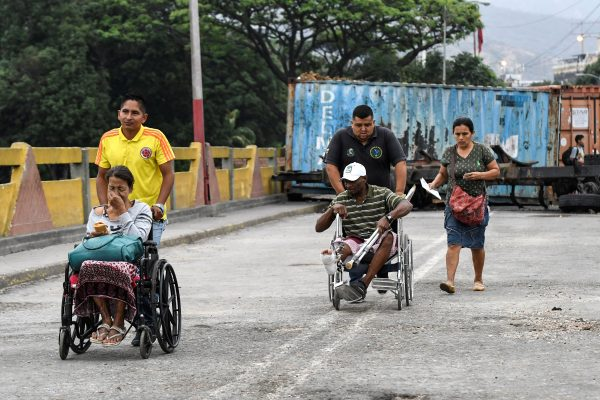 People are wheeled across the Simon Bolivar International Bridge