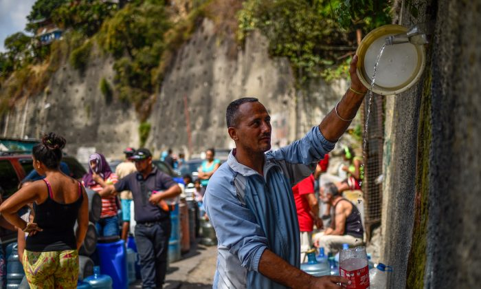 """A man fills containers with water flowing down from the Wuaraira Repano mountain, also called """"El Avila"""", in Caracas on March 13, 2019. Millions in Venezuela have been left without running water.(Federico Parra/AFP/Getty Images)"""