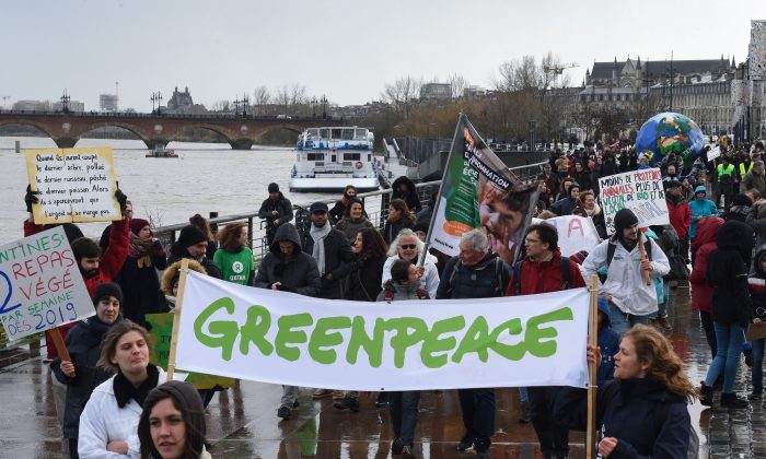 """People hold a banner reading """"Greenpeace"""" as they take part in a march for the climate, in Bordeaux, on January 27, 2019. MEHDI FEDOUACH/AFP/Getty Images"""