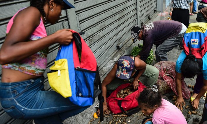 People collect food from the floor after a street market was looted in Caracas, on March 10, 2019. (Ronaldo Schemidt/AFP/Getty Images)