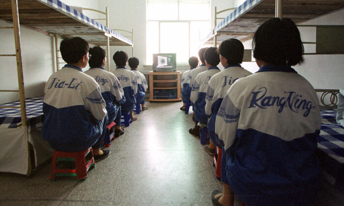 "Falun Gong practitioners are shown in Masanjia labor camp watching a video meant to ""reeducate"" them during a propaganda tour arranged by the camp authorities on May 22, 2001. (John Leicester/AP Photo)"