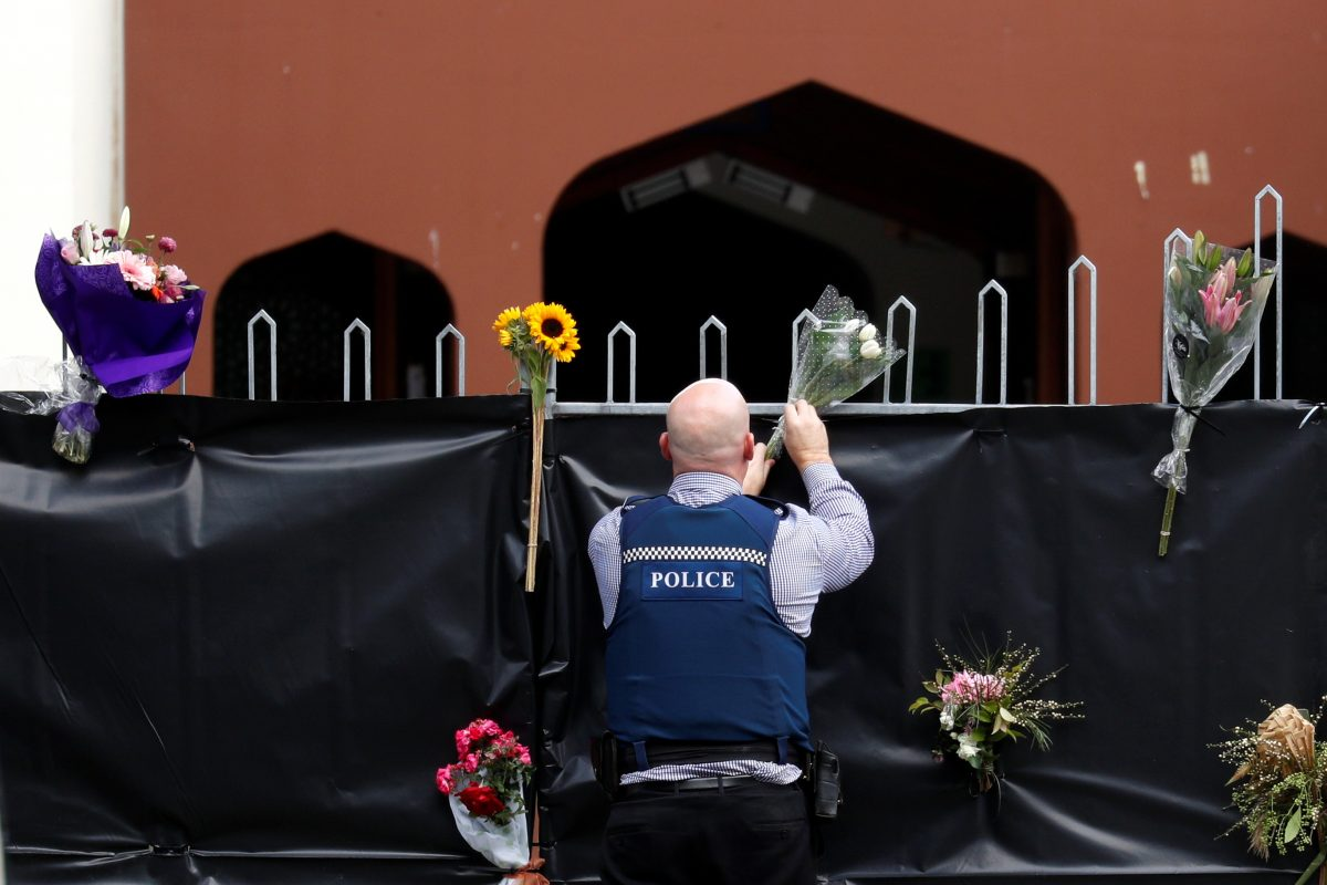 police officer places flowers at the entrance of Masjid Al Noor mosque