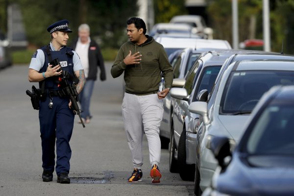 Ash Mohammed, right, talks to a police officer about his father and two brothers who are missing near the Masjid Al Noor mosque