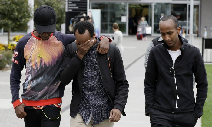 Abdifatah Ibrahim (C), and his brother Abdi (R), walk with an unidentified friend in Christchurch, New Zealand, on March 17, 2019, their 3-year-old brother Mucaad the youngest victim. (Mark Baker via AP)