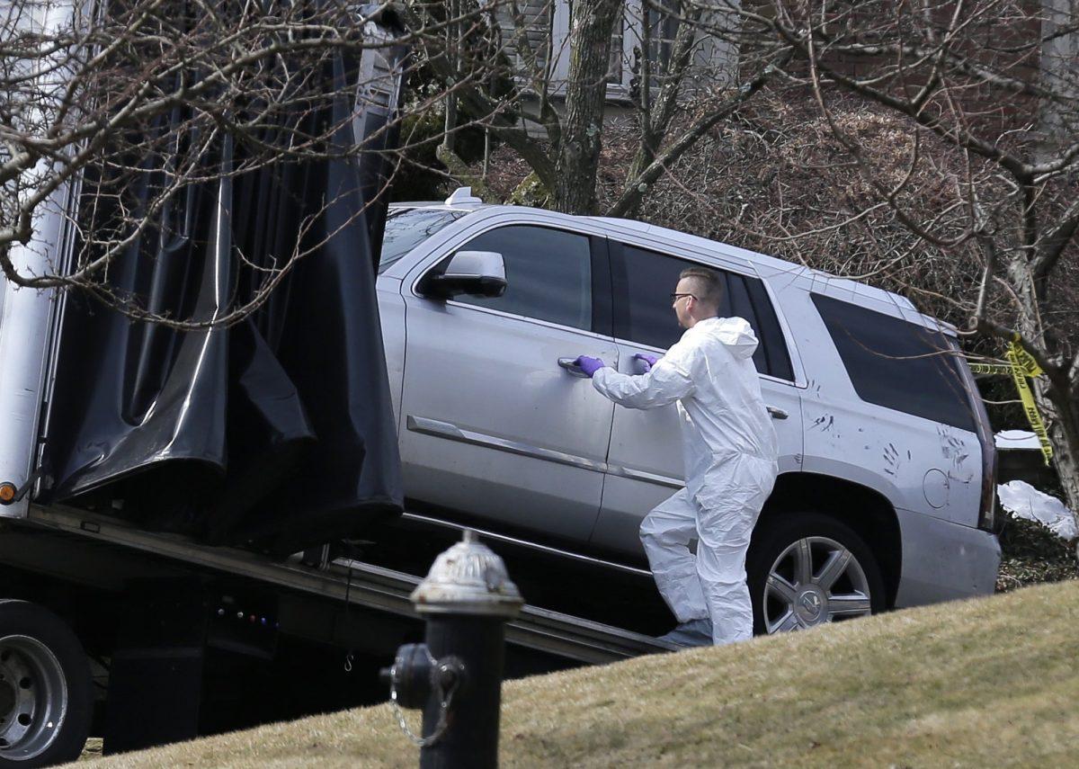 Crime scene investigators load a car