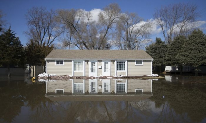 The Rock River crested its banks and floods a home on Old Harlem Road on March 16, 2019, in Machesney Park, Ill. Some homes are flooding in northern Illinois as waters rise on the Pecatonica and Rock rivers. The National Weather Service on Saturday said record crests are possible along both rivers. (Scott P. Yates/Rockford Register Star via AP)