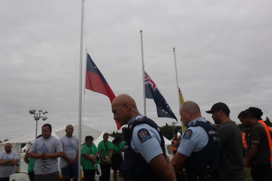 People gather around flags at half-mast