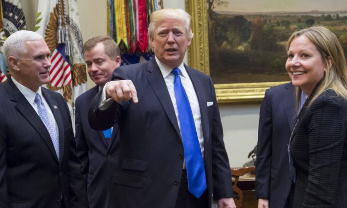 President Donald Trump greets General Motors CEO Mary Barra (R) alongside US Vice President Mike Pence (L) prior to a meeting with automobile industry leaders in the Roosevelt Room of the White House in Washington on Jan. 24, 2017. (Saul Loeb/AFP/Getty Images)