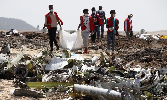 FILE PHOTO: Ethiopian Red Cross workers carry a body bag with the remains of Ethiopian Airlines Flight ET 302 plane crash victims at the scene of a plane crash, near the town of Bishoftu, southeast of Addis Ababa, Ethiopia March 12, 2019. REUTERS/Baz Ratner