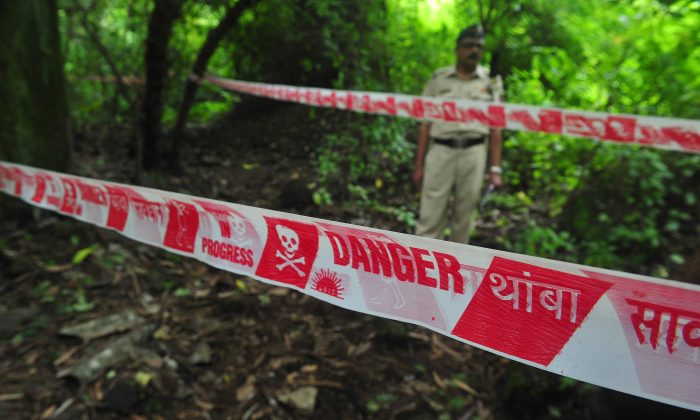 In this file image policeman keeps watch near a police cordon of the crime scene in the Shakti Mills area, where a female photographer was gang-raped overnight, in Mumbai on August 23, 2013. (Indranil Mhukherjee/AFP/Getty Images)