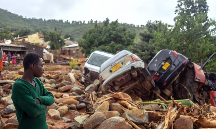 A man stands next to the wreckage of vehicles washed away on March 18, 2019, in Chimanimani, eastern Zimbabwe, after the area was hit by the cyclone Idai. (Zinyange Auntony/AFP/Getty Images)