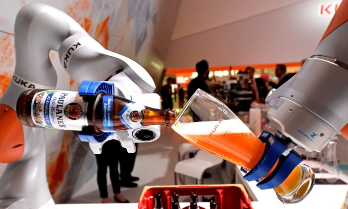 "A robotic arm fills a glass with Bavarian Weiss beer at the booth of German company Kuka at the world's biggest industrial fair, ""Hannover Fair,"" in Hanover, Germany on April 24, 2017. (Fabian Bimmer/Reuters)"