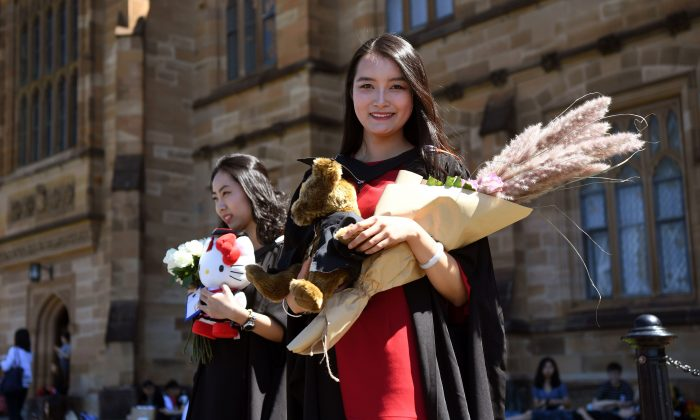 Student Zheng Zizan from Xian in China poses for family photos after graduating with a Masters of Commerce from Sydney University on Oct. 12, 2017. (William West/AFP/Getty Images)