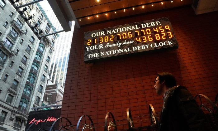 A man walks past the he National Debt Clock on 43rd Street in midtown New York City February 15, 2019. - The National Debt Clock is a billboard constantly updating to display the current United States gross national debt and each American family's share of the debt. TIMOTHY A. CLARY/AFP/Getty Images