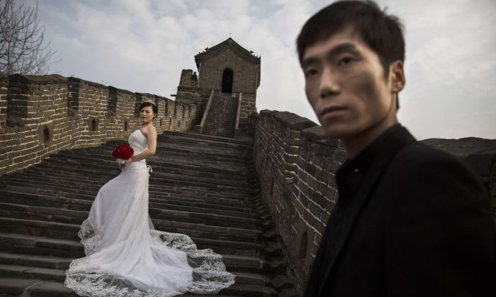 A Chinese bride poses for a wedding photographer as her groom looks on, on a section of the Great Wall of China near Beijing on October 28, 2014. China's marriage rate decreased continually for the past five years and reached the lowest point in 2018. (Kevin Frayer/Getty Images)