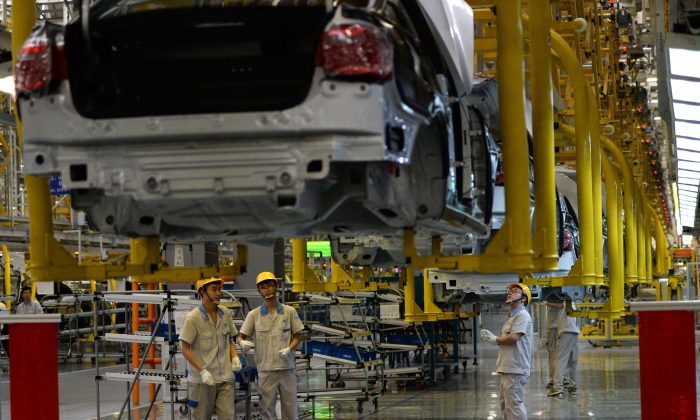 Chinese auto workers on the assembly line at the FAW-Volkswagen plant in Chengdu City, in southwestern China's Sichuan Province, on July 6, 2014. (GOH CHAI HIN/AFP/Getty Images)