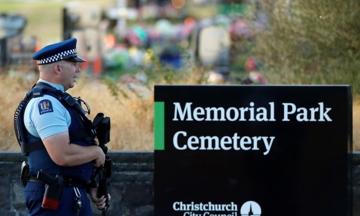An armed policeman stands guard as the burial ceremony of the victims of the mosque attacks, at the Memorial Park Cemetery in Christchurch, New Zealand, on March 20, 2019. (Jorge Silva/Reuters)