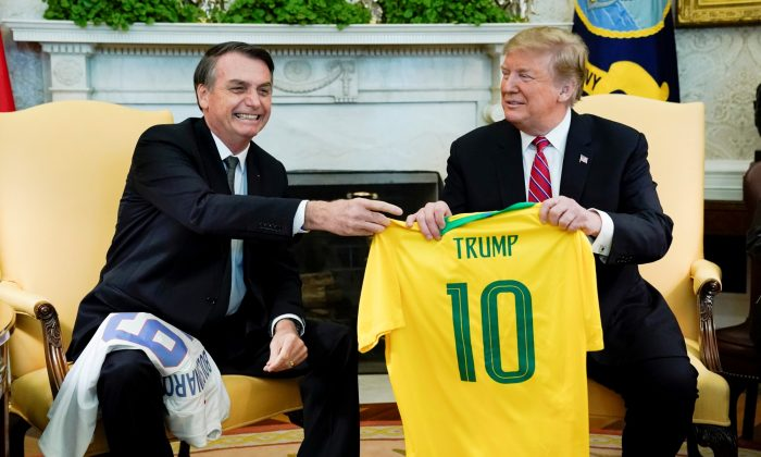 Brazil's President Jair Bolsonaro presents a Brazil national soccer team jersey to U.S. President Donald Trump during a meeting in the Oval Office of the White House on March 19, 2019. (Kevin Lamarque/Reuters)