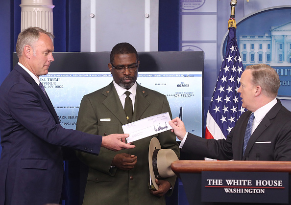 White House press secretary Sean Spicer (R) gives Interior Secretary Ryan Zinke (L) the first quarter check of U.S. President Donald Trump's salary, which he donated to the National Park Service as Tyrone Brandyburg (C), Harpers Ferry National Historical Park superintendent, looks on during the daily press briefing at the White House, on April 3, 2017 (Mark Wilson/Getty Images)
