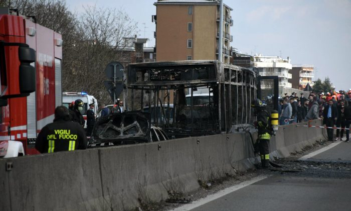 Firefighters stand by the gutted remains of a bus in San Donato Milanese, near Milan, Italy, on March 21, 2019. (Daniele Bennati/ANSA via AP)
