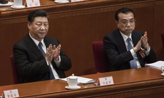 Chinese leader Xi Jinping, left, and Prime Minister Li Keqiang applaud during the third plenary session of the National People's Congress at The Great Hall Of The People on March 12, 2019 in Beijing, China. Kevin Frayer/Getty Images