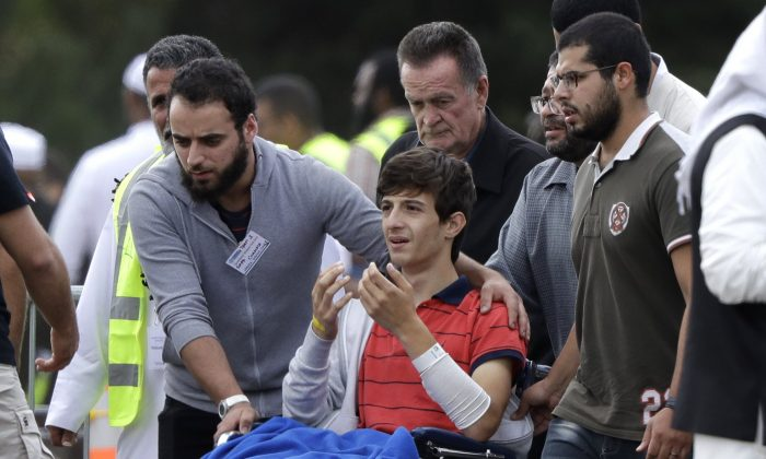 Zaed Mustafa, in wheelchair, brother of Hamza and son of Khalid Mustafa killed in the March 15 mosque shootings reacts during their burial at the Memorial Park Cemetery in Christchurch, New Zealand, on March 20, 2019. (Mark Baker/AP Photo)