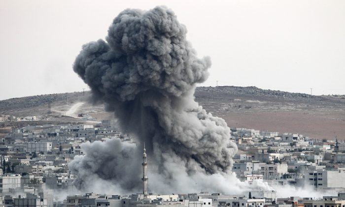 Heavy smoke rises following an airstrike by the US-led coalition aircraft in Kobani, Syria, during fighting between Syrian Kurds and the ISIS terrorists, as seen from the outskirts of Suruc, on the Turkey-Syria border, on Oct. 18, 2014. (Gokhan Sahin/Getty Images)