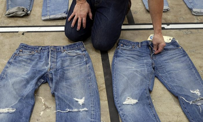 Bart Sights, head of the Eureka Lab, compares the markings and damage on jeans that he guesses are close to 30 years old, left, to jeans made within a few hours of this photograph at Levi's innovation lab in San Francisco, California, on March 21, 2019. (Jeff Chiu/AP Photo)
