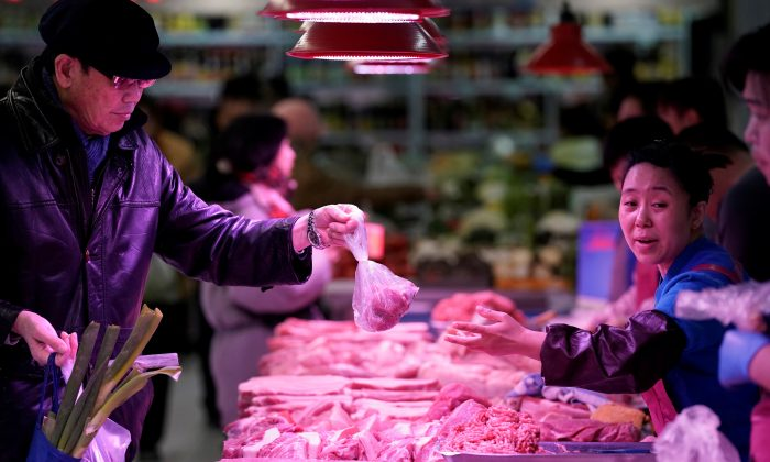A resident gets pork from a vendor at a market in Beijing on Dec. 26, 2018. (Jason Lee/Reuters)