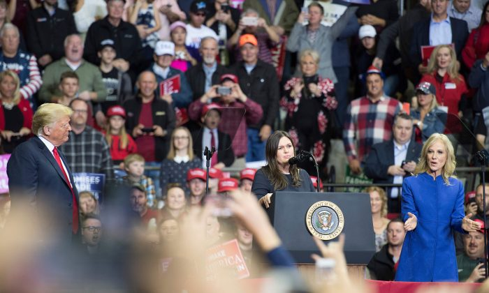 President Donald Trump (L) looks on as White House Press Sarah Huckabee Sanders speaks and Kellyanne Conway cheers at a Make America Great Again rally in Fort Wayne, Indiana on Nov. 5, 2018. (JIM WATSON/AFP/Getty Images)