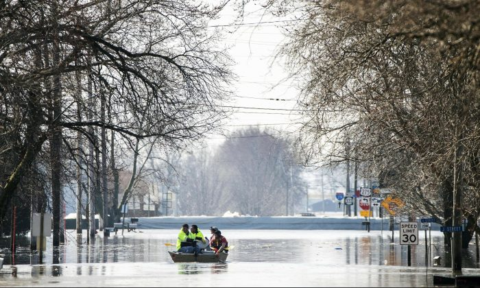 People on a boat float down floodwaters that cover Washington Street, in Hamburg, Iowa, on March 20, 2019. (Chris Machian/Omaha World-Herald via AP)