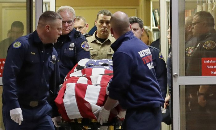 The body of a Kittitas County Sheriff's deputy is draped with a U.S. flag as it is carried out of Kittitas Valley Healthcare Hospital in the early morning hours of March 20, 2019, in Ellensburg, Wash. (Ted S. Warren/AP Photo)