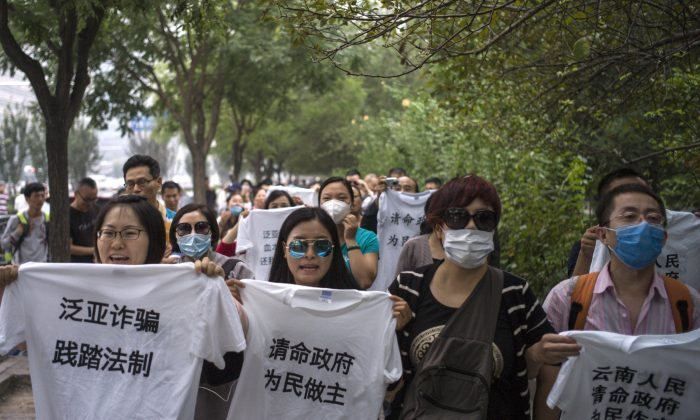 People protest outside the office of China's top anti-graft agency complaining they were tricked by Fanya Metals Exchange. Chinese investors who claim to have lost money on risky investments mounted a rare protest in Beijing on Sept. 22, 2015. (Fred Dufour/AFP/Getty Images)