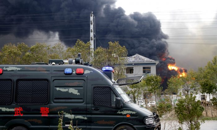 A vehicle of paramilitary police is seen near smoke following an explosion at a chemical industrial park in Yancheng City, Jiangsu Province, China on March 21, 2019. (Stringer via Reuters)