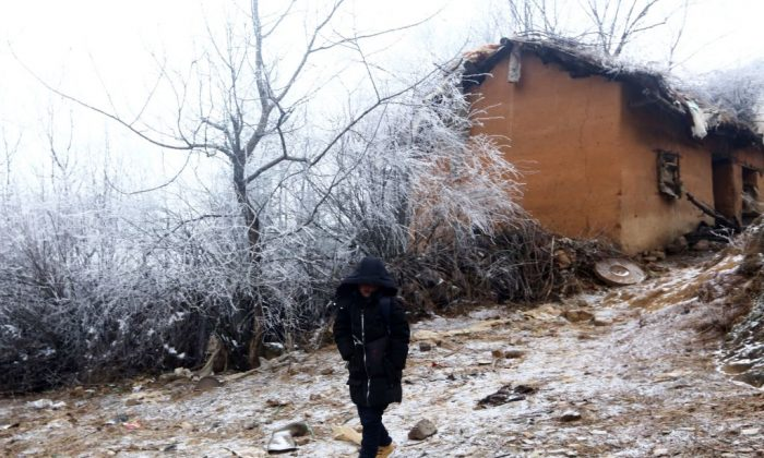 """Wang Fuman, also known as """"Frost Boy,"""" walks on the road in Ludian in China's southwestern Yunnan Province on Jan. 12, 2018. (AFP/Getty Images)"""