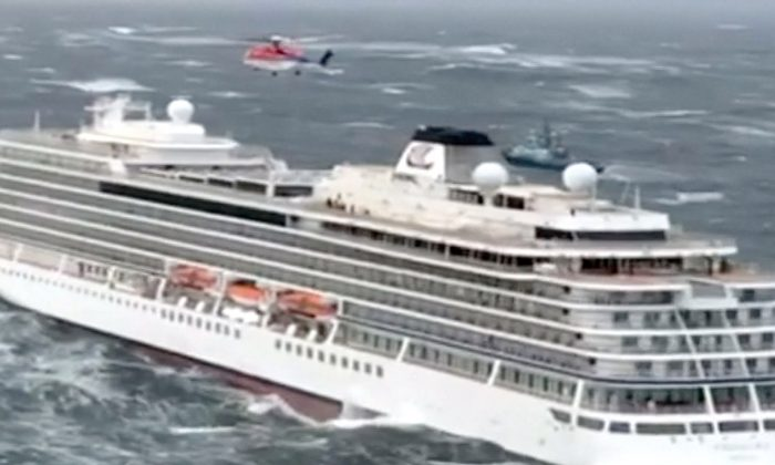 Viking Sky cruise ship with helicopter hovering above it in Hustadvika, Norway, on March 23, 2019. (CHC Helicopters via Reuters)