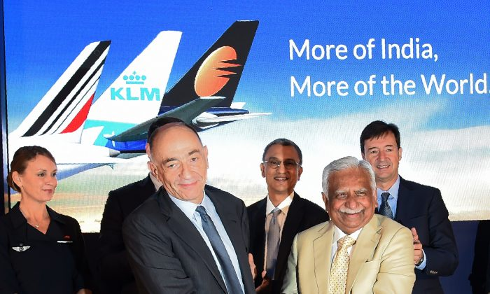 Jean-Marc Janaillac (2L), Chief Executive Officer of Air France-KLM  shakes hands with Naresh Goyal (2R), founder Chairman of Jet Airways, after signing an agreement during a press conference in Mumbai on November 29, 2017.