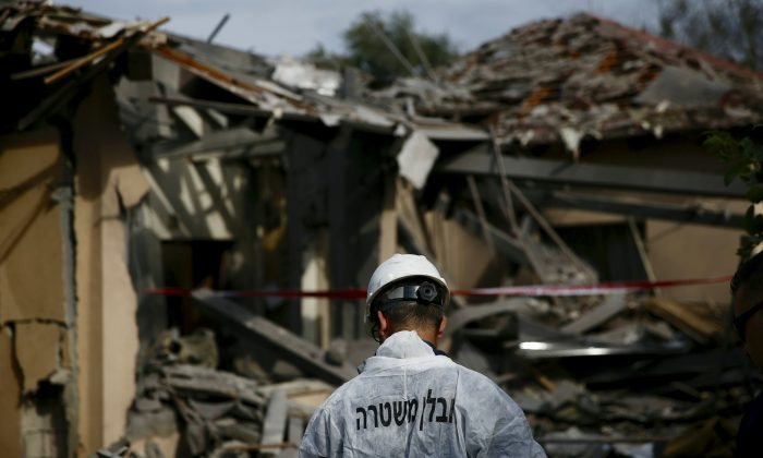 An Israeli police officer inspects the damage to a house hit by a rocket in Mishmeret, central Israel on March 25, 2019. (Ariel Schalit/Photo via AP)