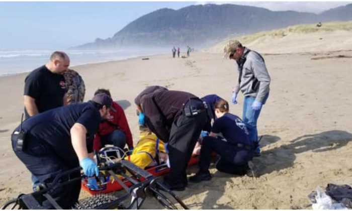 A rescue team attends to a woman hit by a log on  Manzanita Beach, Oregon, on March 23, 2019. (Nehalem Bay Fire & Rescue)