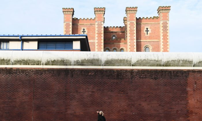 Two people walk alongside the curtain wall of HMP Liverpool, northwest England, on Nov. 15, 2016. (Paul Ellis/AFP/Getty Images)