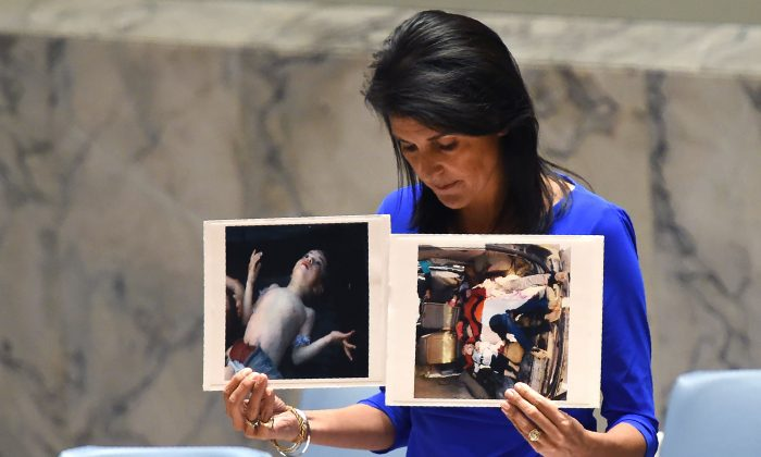 U.S. Ambassador to the UN Nikki Haley holds photos of victims of a suspected chemical attack in Syria, as she speaks as the UN Security Council in New York on April 5, 2017. (TIMOTHY A. CLARY/AFP/Getty Images)