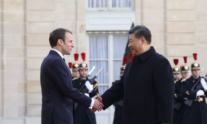 French President Emmanuel Macron (L) welcomes Chinese leader Xi Jinping at the Elysee Palace in Paris, on March 25, 2019, during a state visit. (Ludovic Marin/AFP/Getty Images)