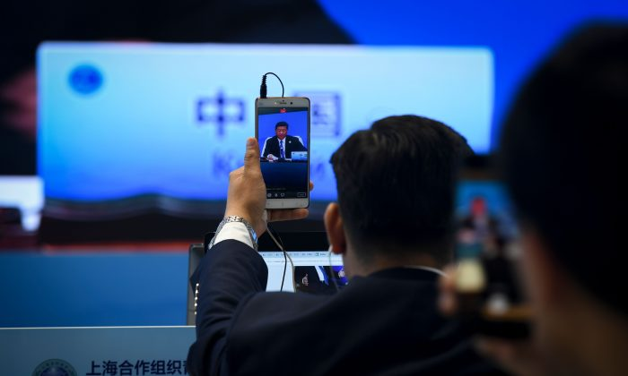 A journalist uses his mobile phone to broadcast live footage as a giant video screen (background) shows Chinese leader Xi Jinping speaking during Shanghai Cooperation Organisation Summit in Qingdao, China's Shandong Province on June 10, 2018. (Wang Zhao/AFP/Getty Images)