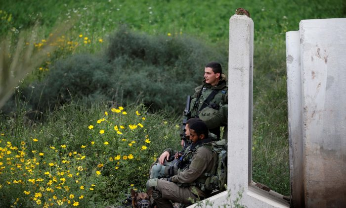 Israeli soldiers lean against a concrete barrier block near the border with Gaza, in southern Israel