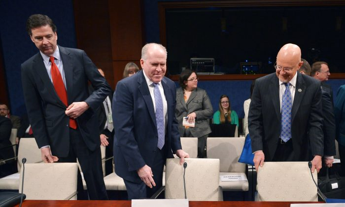 (L-R) FBI Director James Comey, CIA Director John Brennan, and Director of National Intelligence James Clapper take their seats for a House Select Intelligence Committee hearing on Feb. 4, 2014. (MANDEL NGAN/AFP/Getty Images)