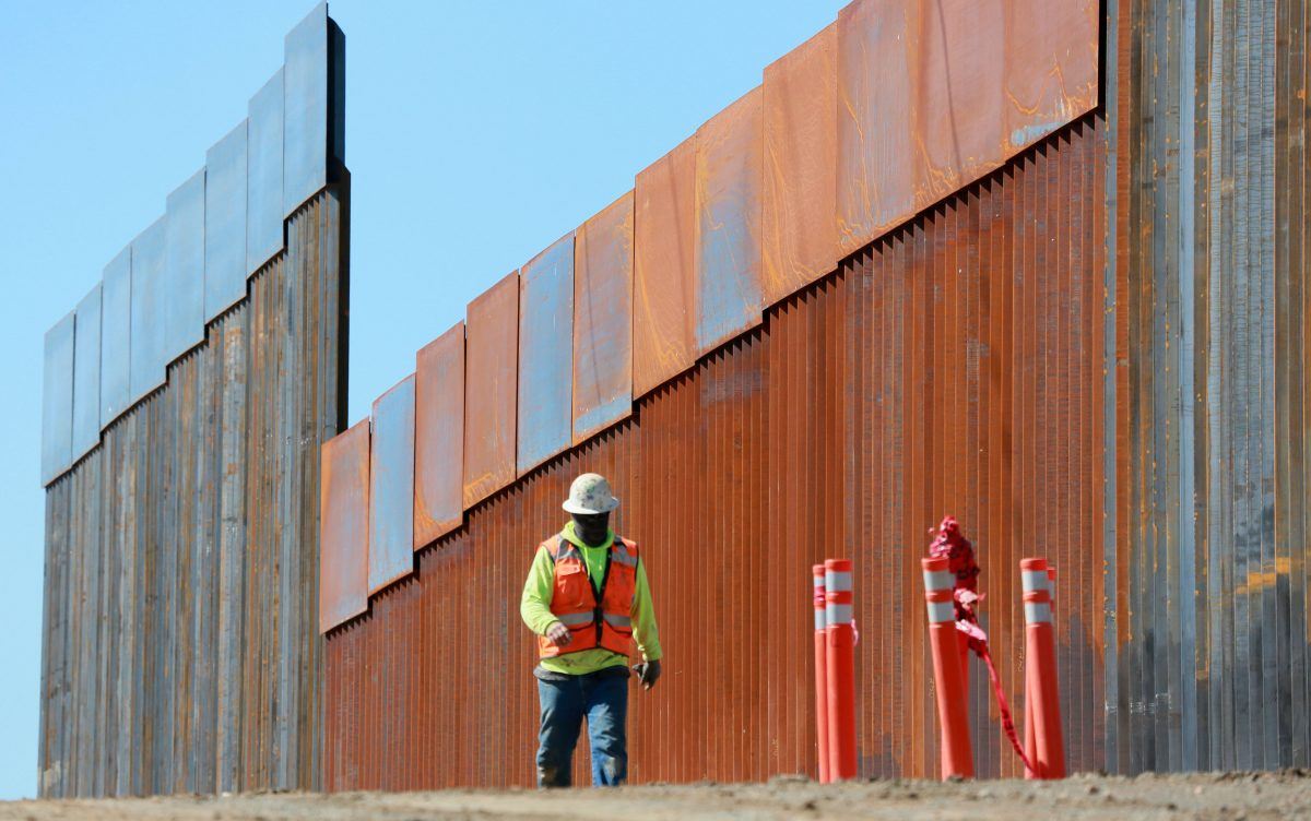 Construction workers build a secondary border wall in Otay Mesa