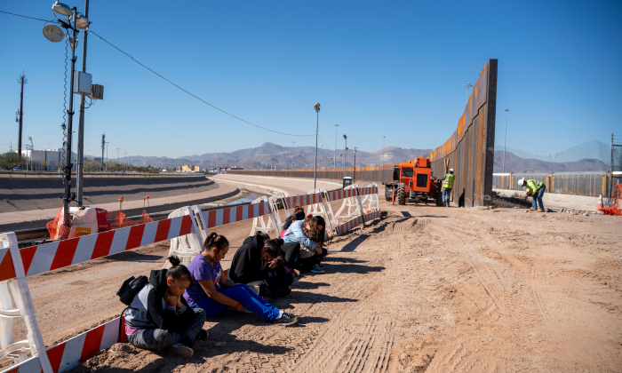 Salvadoran illegal aliens wait for a transport to arrive after turning themselves into U.S. Border Patrol by border fence under construction in El Paso, Texas, on March 19, 2019. (Paul Retje/AFP/Getty Images)