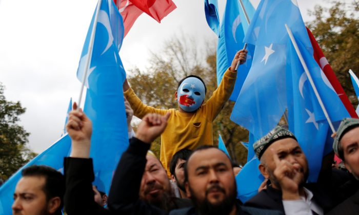 A masked Uyghur boy takes part in a protest against China, at the courtyard of Fatih Mosque, a common meeting place for pro-Islamist demonstrators in Istanbul, Turkey on Nov. 6, 2018. (Murad Sezer/Reuters)