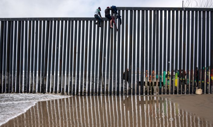 Central American migrants sit above the US-Mexico border fence as a Border Patrol agent stands guard, as seen from Tijuana to San Diego  as seen from Playas de Tijuana, in Baja California state, Mexico, on March 21, 2019.  (Guillermo Arias/AFP/Getty Images)