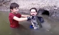 Dad Asks Son to Lower Arm Into Dark Hole Only to Pull Out a Monster Fish As Big As Him
